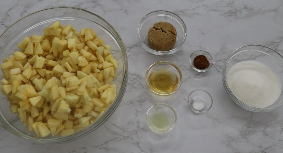ingredients for apple crisp. bowls of apples, brown sugar, white sugar, cinnamon, apple juice, lemon juice, and salt