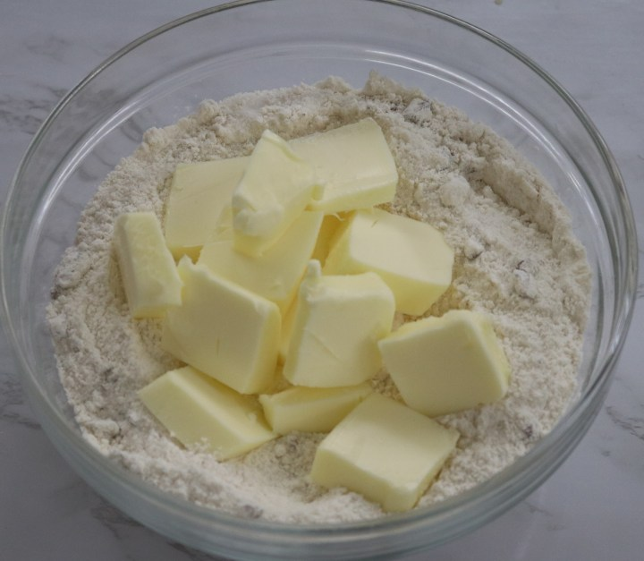 Butter on top of crisp topping mix in a clear bowl