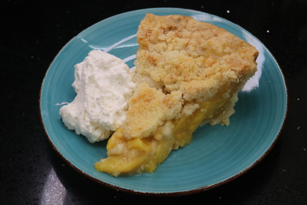 Piece of peach pie with the filling on the bottom and a golden brown crumble topping on the top and a side of thick  cinnamon whipped cream on a blue plate