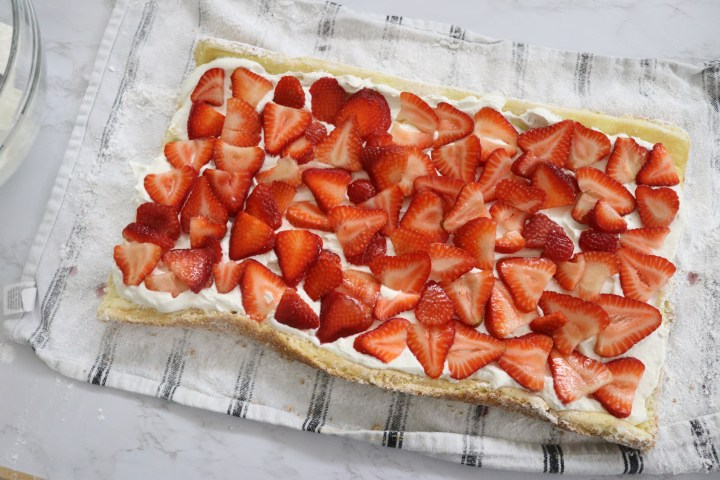 Sliced strawberries 0on whipped cream laying on a cake