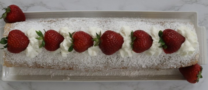 A white tray with a cake roll covered in confectioners sugar and decorated with strawberries and whippd cream