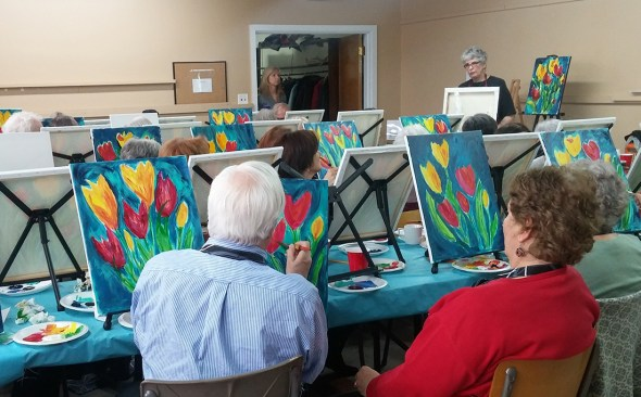 Judy Csukly leads Our Harbour supporters painting their blooms of spring.
