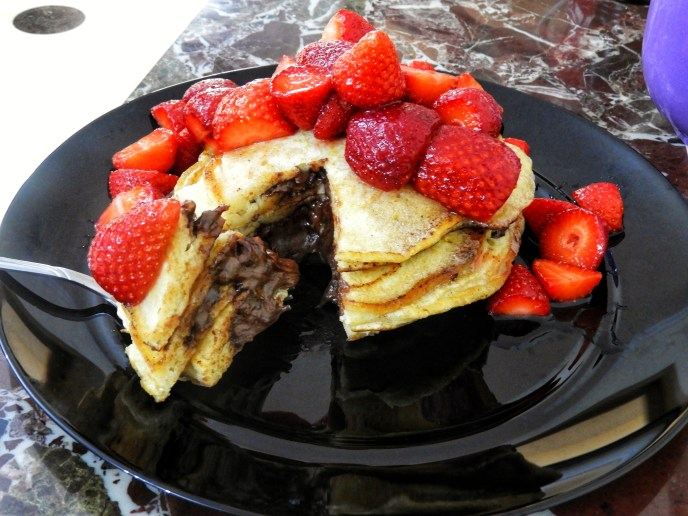 Nutella-Stuffed Pancakes topped with a cascading mound of Macerated Strawberries