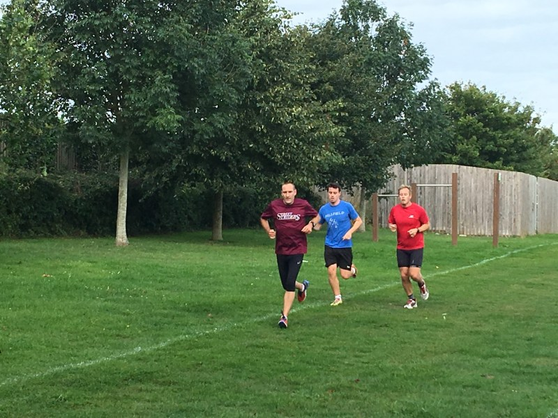 European motorhome traveler Paul from ourleapoffaith leading the pack at the street ParkRun in Somerset - sporting his club colours running colours for the Street Striders