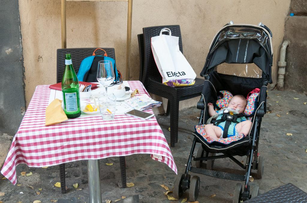 Śpiący niemowlak w wózku podczas zwiedzania Rzymu.