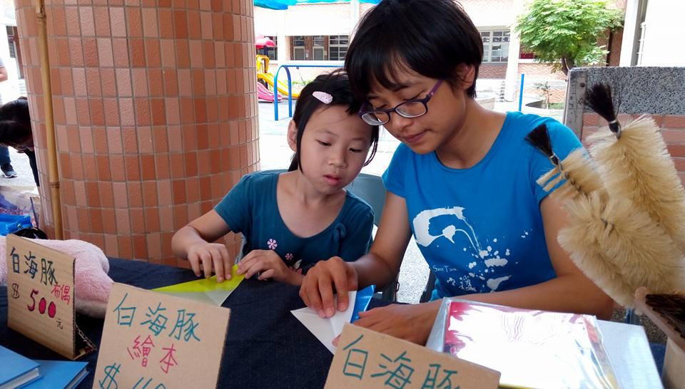 再生市集中大姊姊正在教小朋友摺紙