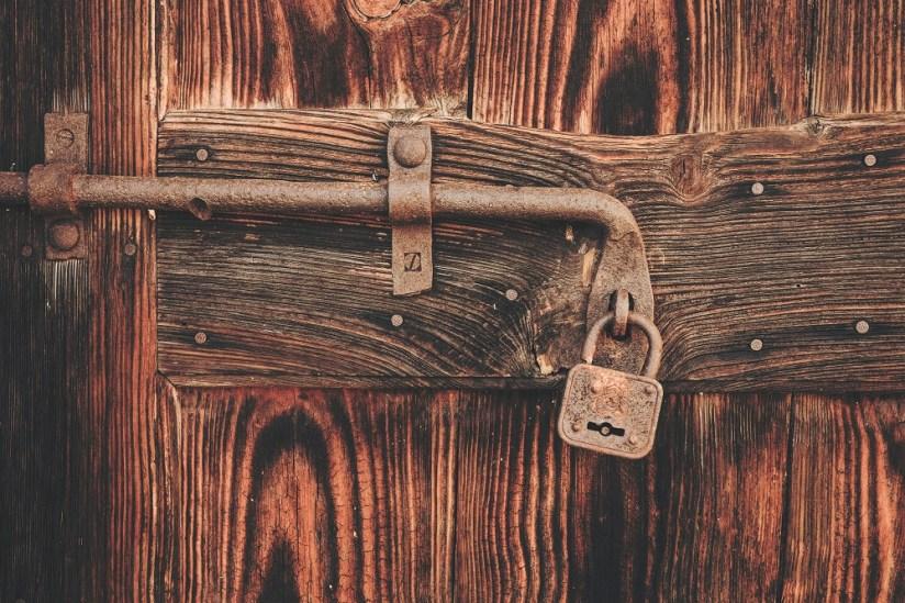Rusty padlock on wooden door