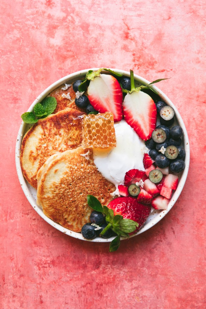 wheat free pancakes with coconut yoghurt and berries on a coral background