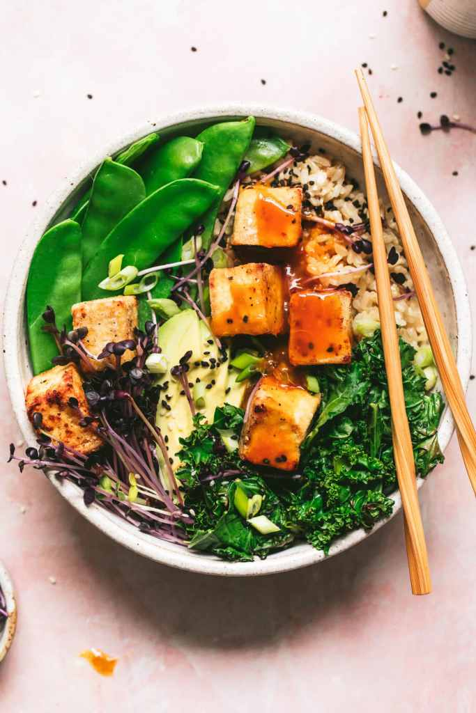 crispy tofu with orange tamari sauce served with snow peas, kale and avocado