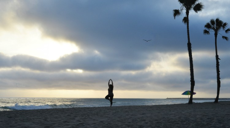 beach yoga kristin oceanside, ca sunset cloudy palm trees
