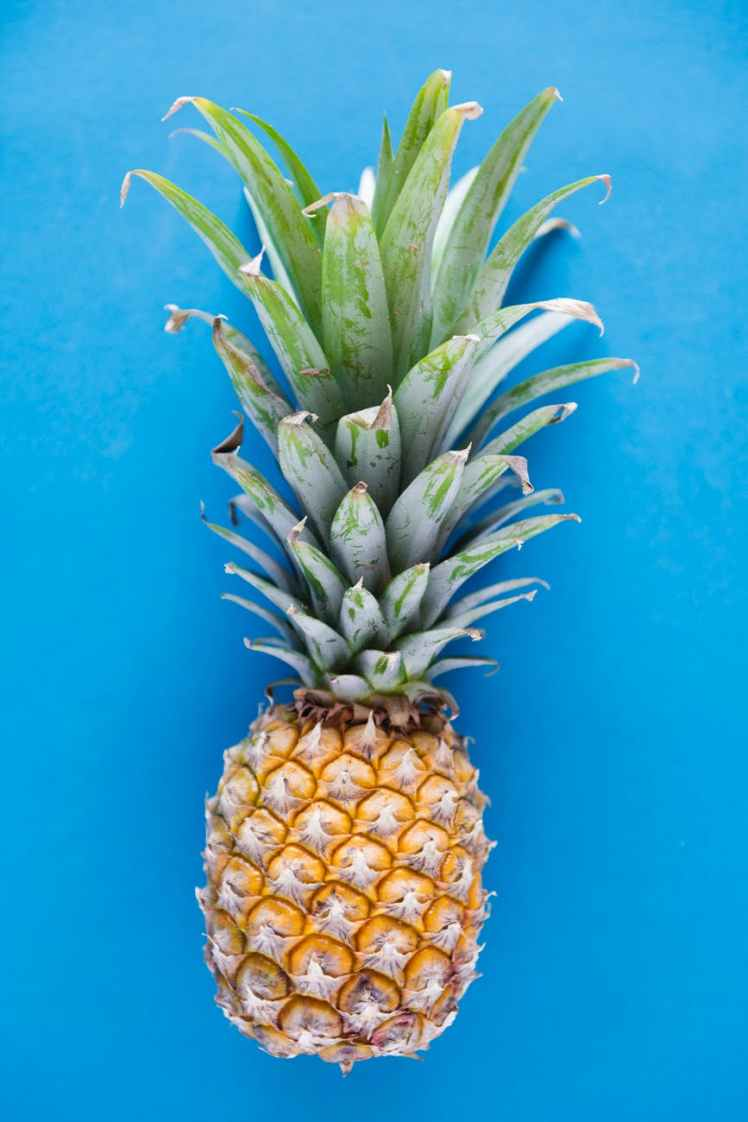 photography of pineapple on blue background