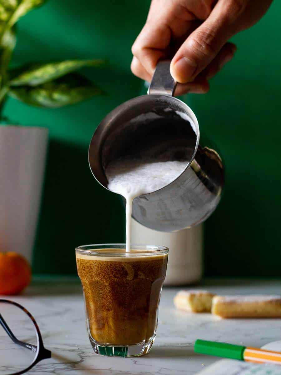 Pouring almond milk on espresso