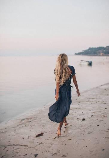 photo of woman walking on seashore