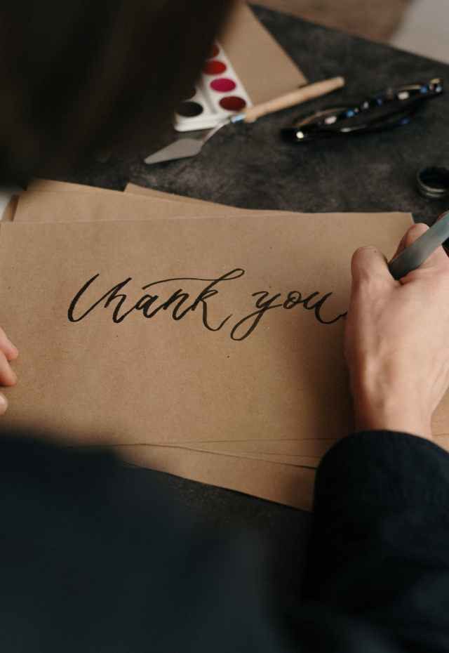 person writing on brown printer paper Are you thankful or grateful