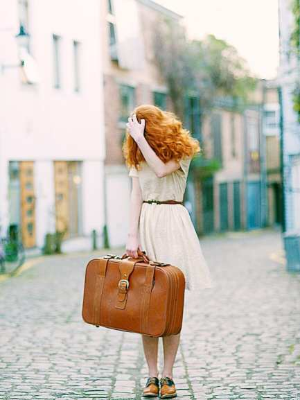woman in white short sleeved dress holding brown leather suitcase good luck superstitions