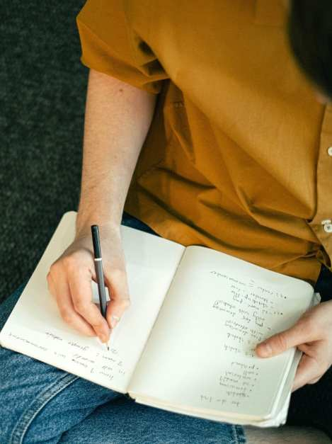 person writing on a notebook