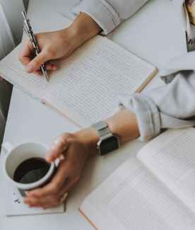 person writing on notebook while holding coffee mug refresh and reset