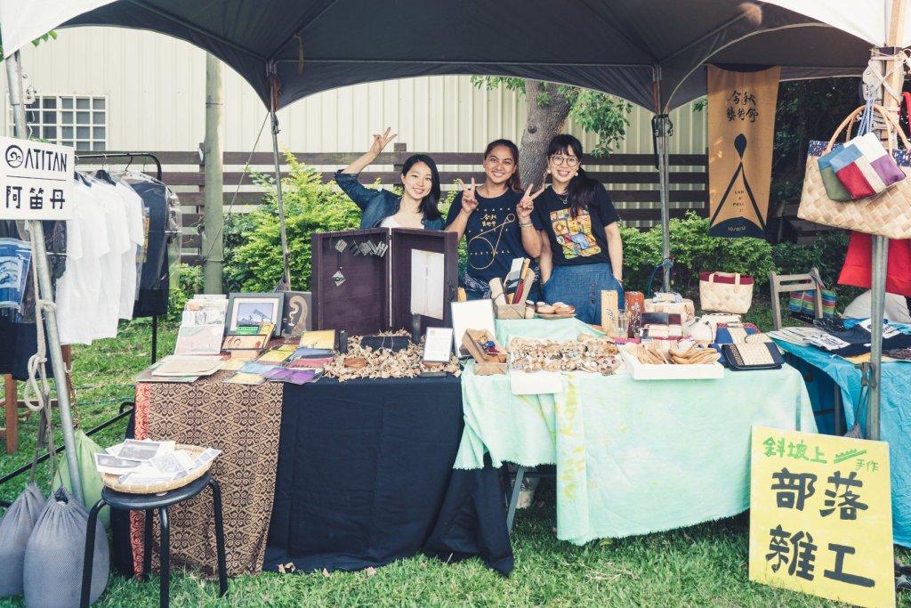 三個部落雜工的女生在草皮上擺市集,有棚子、兩塊桌子