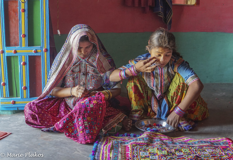 Young girl and mother working on the dowry garments.