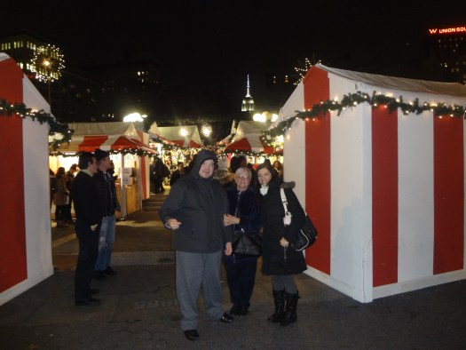 Three people standing by a booth at  Christmas Fair.