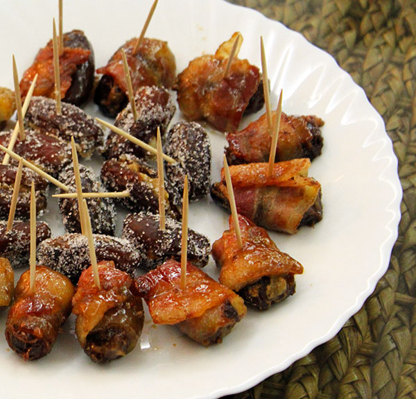 Blue cheese stuffed dates wrapped with bacon and topped with brown sugar. Other dates in center of plate are stuffed with walnuts and rolled in white sugar. http://ourtastytravels.com/blog/easy-tapas-recipe-blue-cheese-stuffed-bacon-wrapped-dates/ #bacon #food #ourtastytravels