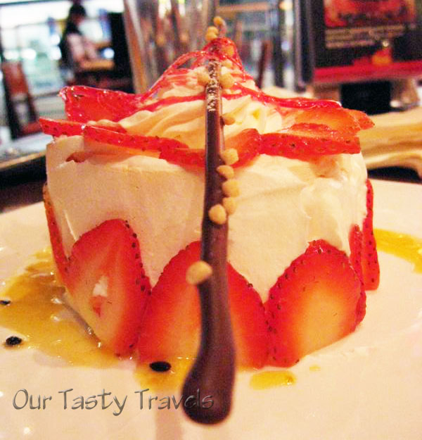 Pavlova decorated with whipped cream, strawberries, and drizzled passionfruit syrup http://ourtastytravels.com/recipes/pavlova-dessert-an-iconic-new-zealand-food/ #dessert #ourtastytravels
