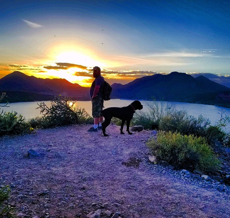 Hiking Butcher Jones Trail  - Hiker and dog at sunset over the lake, on the Butcher Jones Trail at Saguaro Lake, Arizona