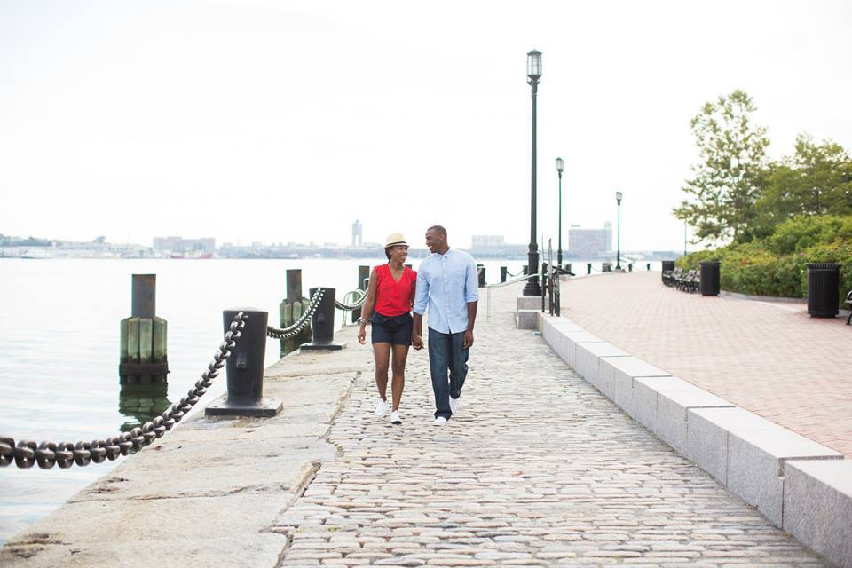 A couple holds hands while walking along the bay.