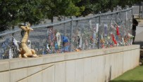 A portion of the protective cyclone fencing still attracts many offerings from visitors.
