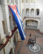 School children beneath the large Cuban flag sharing a tour of the museum.