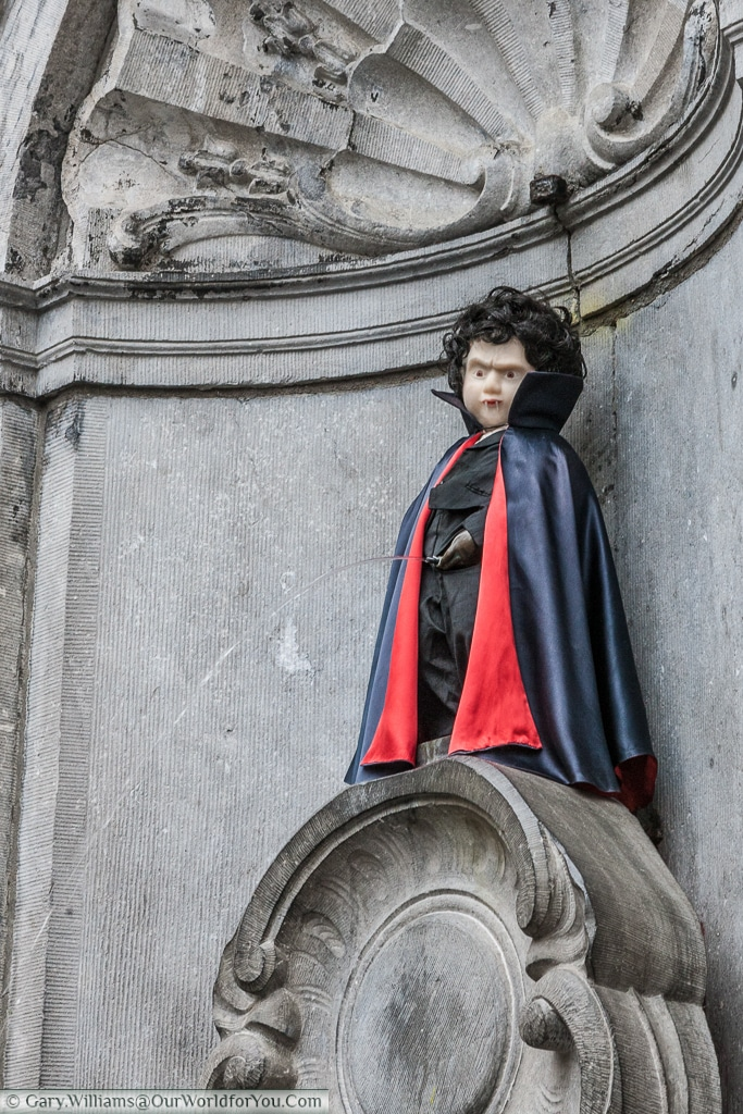 The Manneken Pis in fancy dress performing his usual act in Brussels, Belgium