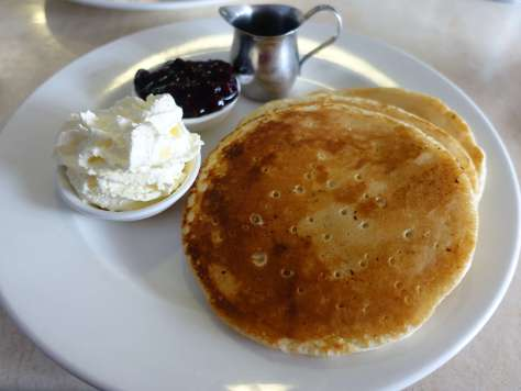 Sweet pancakes with cream, maple syrup and blueberry compote