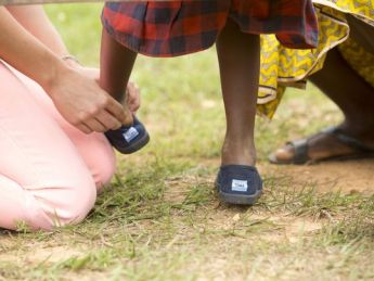 Needy child receiving new shoes on feet