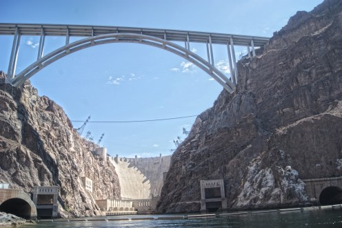 Floating on the Colorado River, Arizona is on the right, Nevada is on the left. Straight ahead is the Mike O'Callaghan - Pat Tillman Memorial bridge with Hoover Dam in the background.