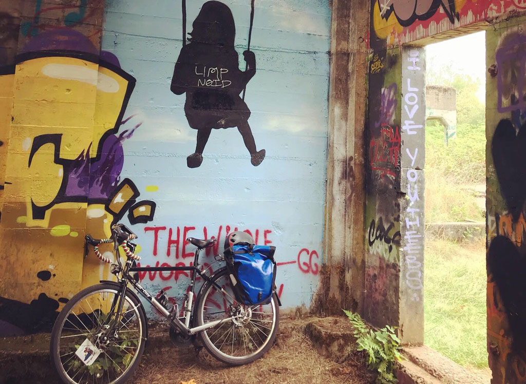 Touring bike leaning against a wall of art and graffiti.
