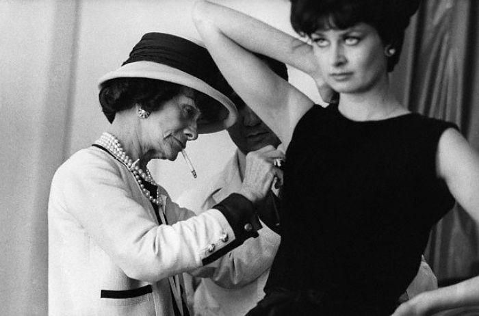 Coco Chanel Adjusting a Model's Dress