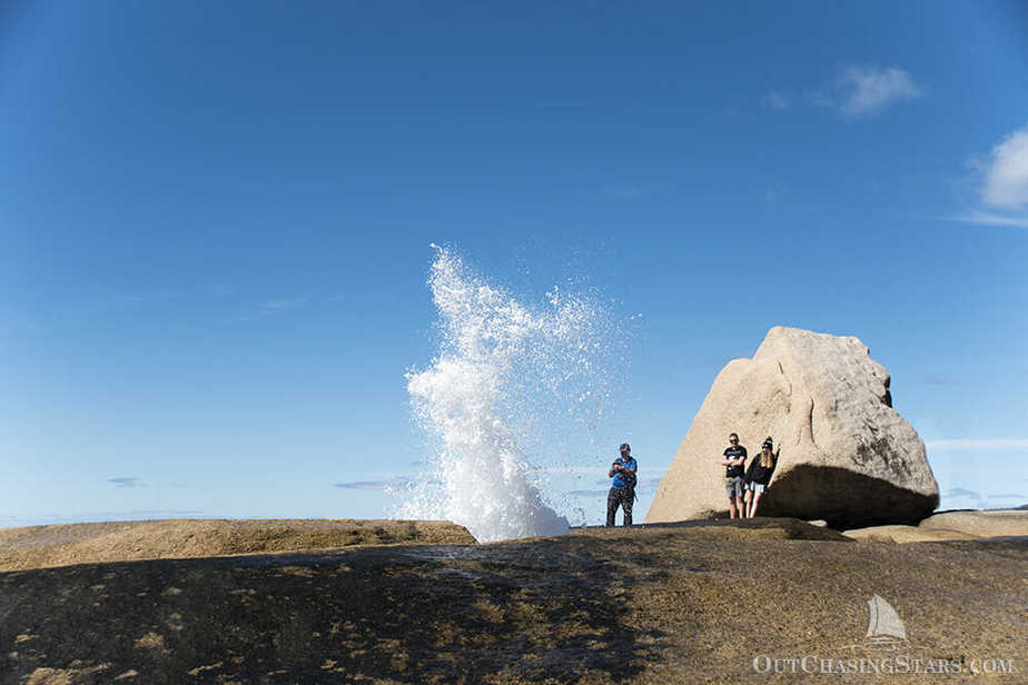 A photograph of three people standing by the Bicheno Blowhole.