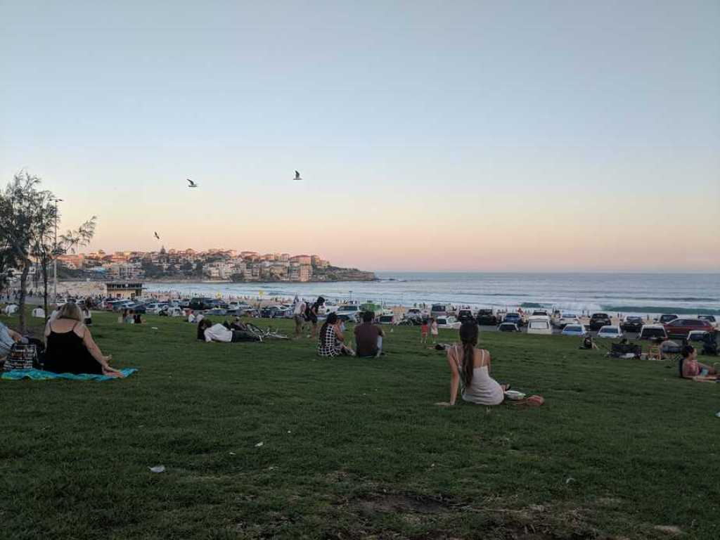 A picture of the sunset on Bondi Beach with lots of people around.