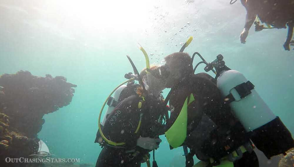 Amy and David kissing while underwater with dive gear on in Ningaloo Reef.