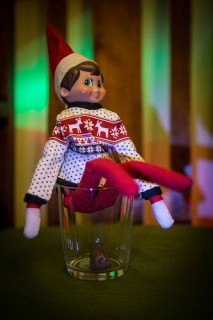 Elf on the shelf makes a mess in a glass. Elf poops are chocolate
