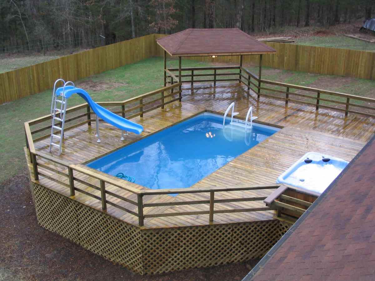42 above ground pools with decks tips ideas design this wooden deck construction is of a more simple and practical design the slat wooden slides allow for access to the workings of the pool while the fully baanklon Image collections