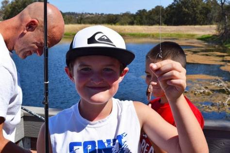 kid holding a fishing line with worm hooked on it