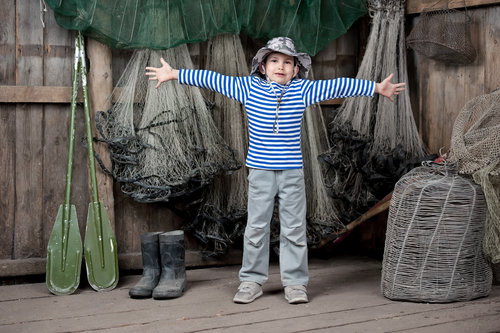 a boy in front of fishing nets