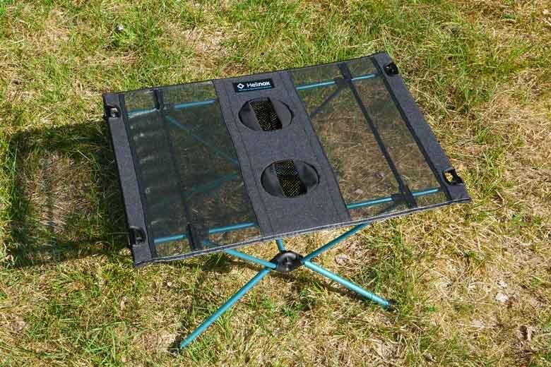 De Helinox Table One heeft een blad van grotendeels gaas en twee bekerhouders.