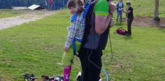 Kind wird mit einem Klettergurt vom Papa hochgehoben