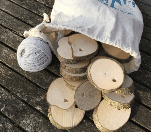 35 drilled wood cookies with ball of string in cotton bag