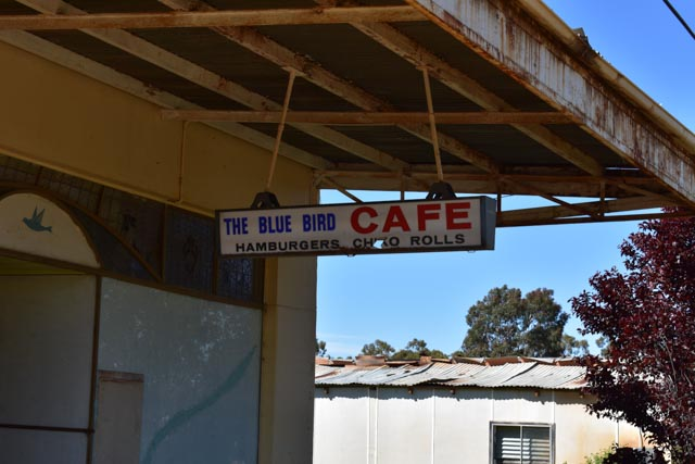 The old sign hanging outside the ling closed Blue Bird Cafe