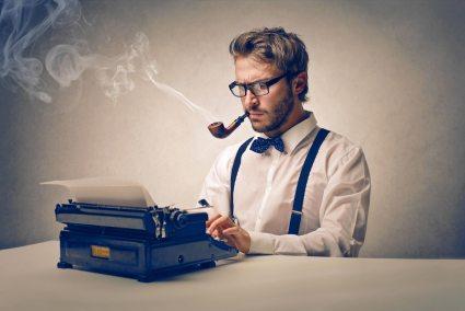 A man smoking a pipe while typing