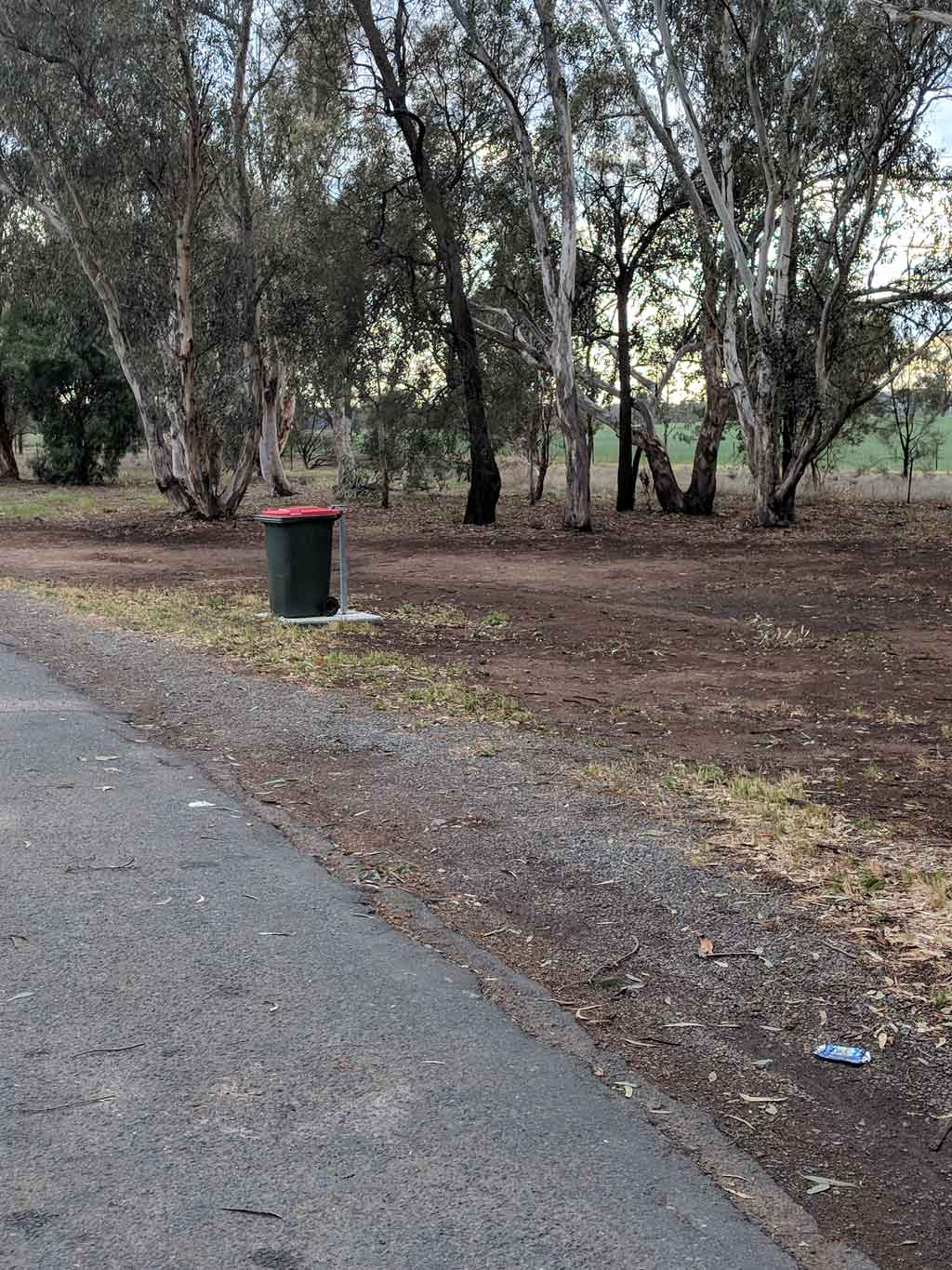A bin in a rest area with crushed can in the foreground