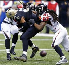 New Orleans Saints tight end Jimmy Graham, center, fumbles after a pass reception near the goal line, between Atlanta Falcons free safety Dezmen Southward (41) and strong safety Kemal Ishmael, in the second half of an NFL football game in New Orleans, Sunday, Dec. 21, 2014. The Falcons won 30-14. (AP Photo/Rogelio Solis)